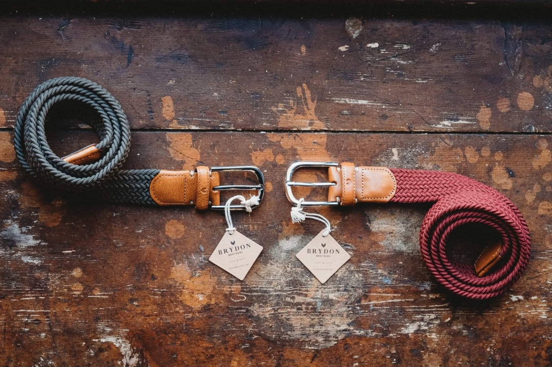 Brydon Brothers Belts on a wooden table, with two designs of men's leather belts and product tags