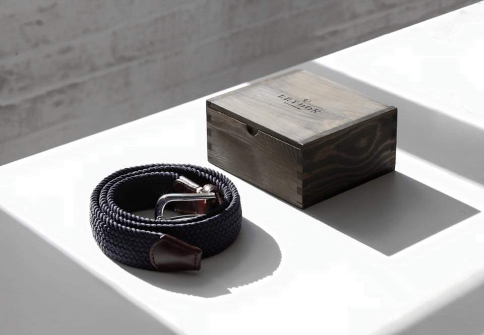 Wooden Box for a Brydon Brothers Belt set on top of a white table in front of a white brick wall