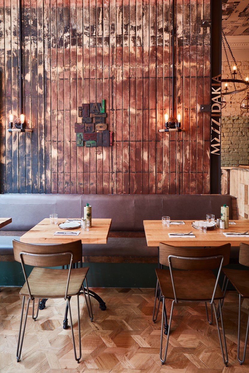 Tables and chairs inside a Mediterranean industrial style restaurant with the work Mezzadakia on the wall