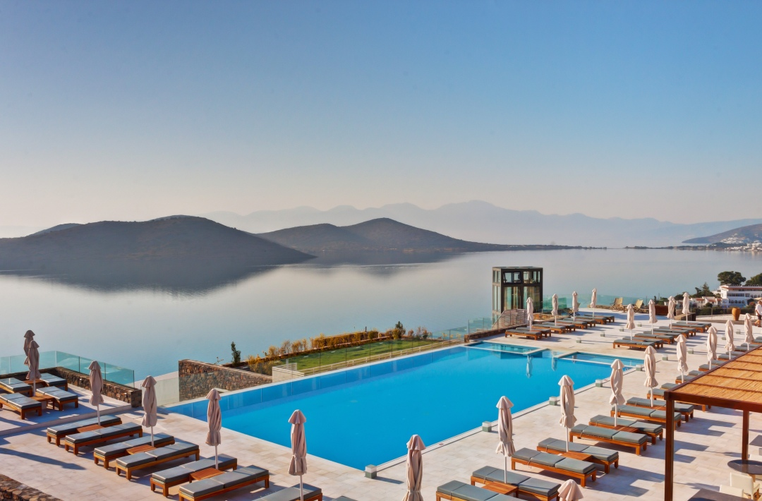 Swimming pool surrounded by luxury sun loungers overlooking the Elounda Bay at the Royal Marmin Bay Boutique Hotel