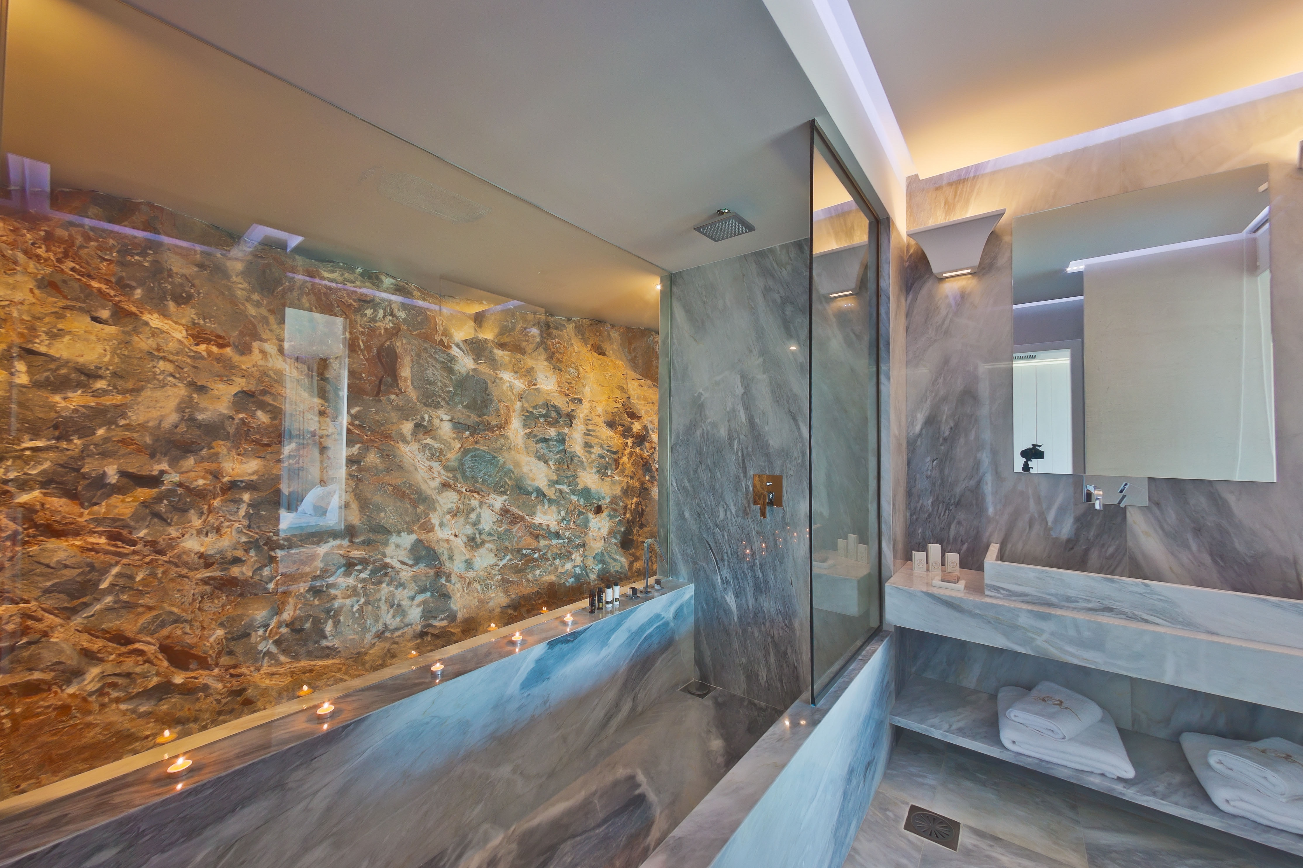 Rich marble bathroom with soft candle lighting around the large bath at the Royal Marmin Bay Boutique Hotel