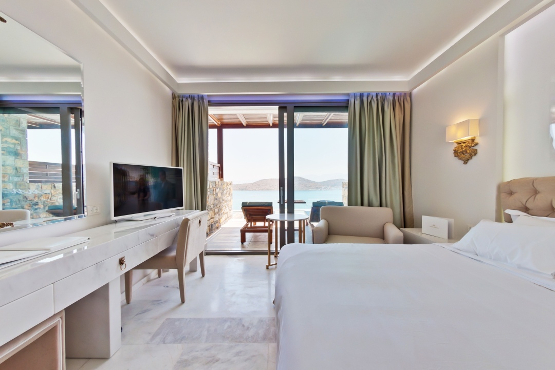 White marble bedroom with a double bed and balcony with seating at the Royal Marmin Bay Boutique Hotel