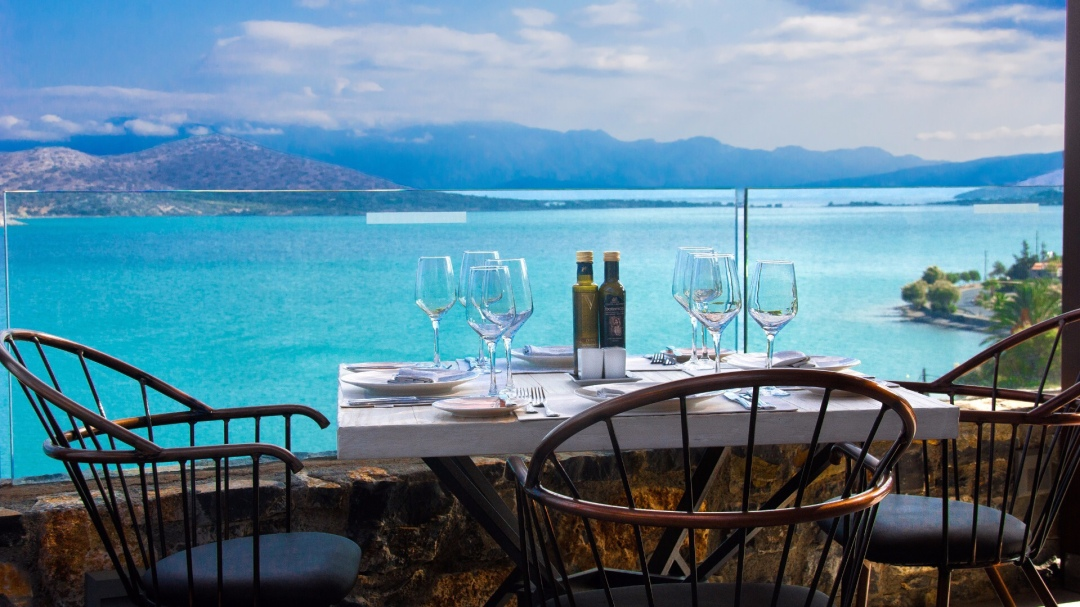 Table and chairs at the restaurant overlooking Elounda Bay at the Royal Marmin Bay Boutique Hotel