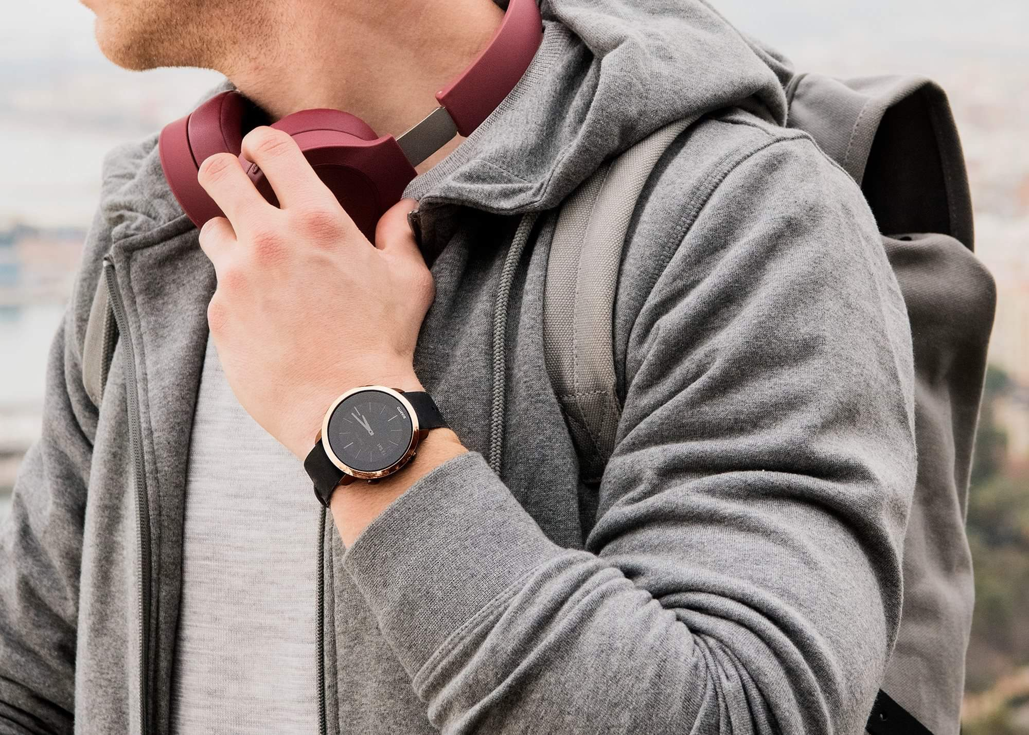 Man in a grey hoodie looks to the left with a black and gold smartwatch on his left wrist