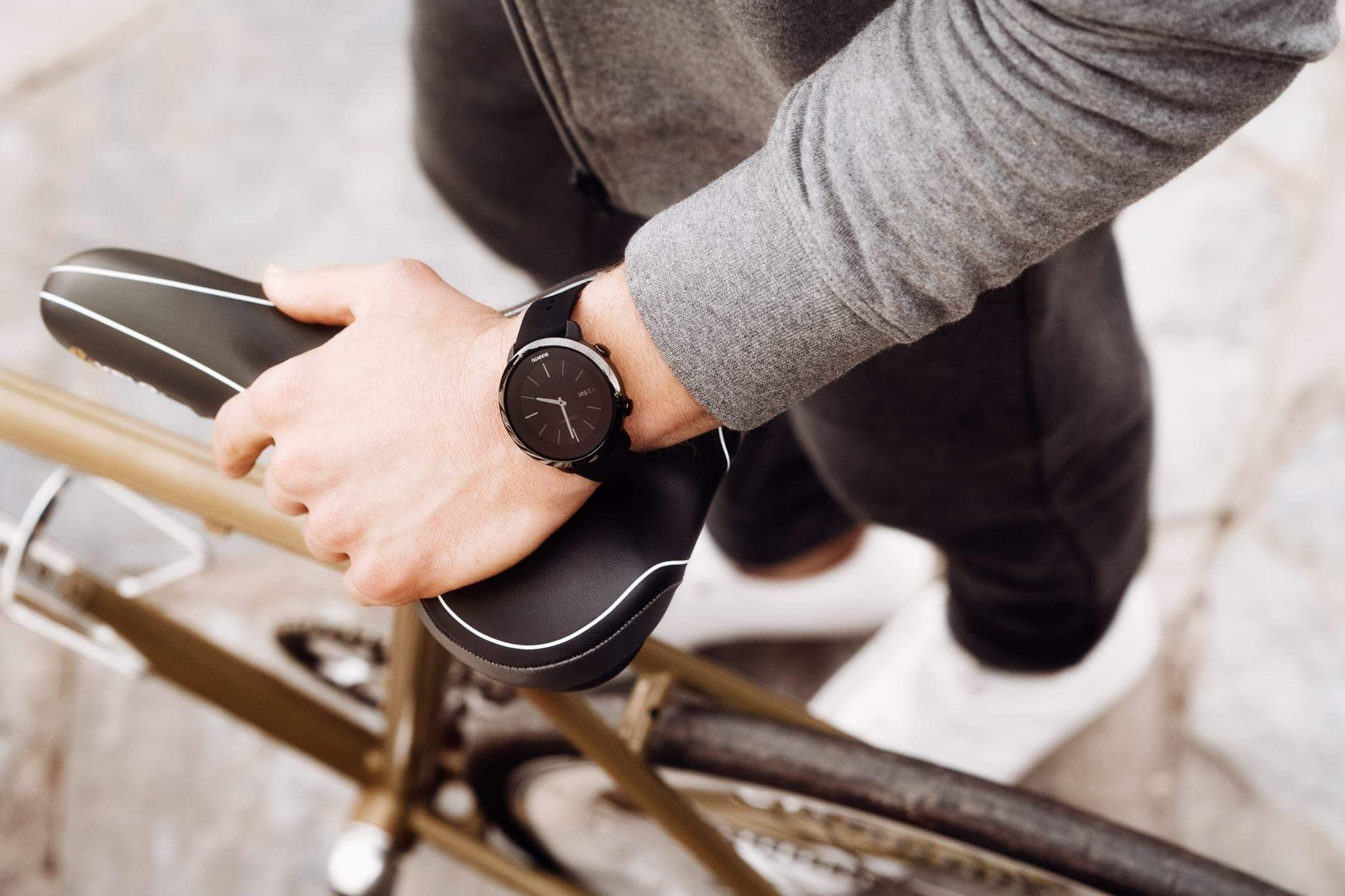 Man in a grey hoodie holding the black leather seat of a bicycle, wearing a black smartwatch that shows a clock face
