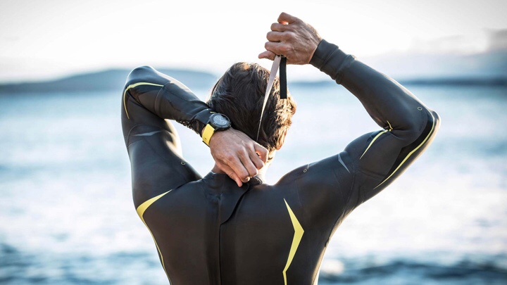 Man in a back wetsuit looks out to the ocean while pulling up the zip, wearing a black and yellow smartwatch on his left wrist