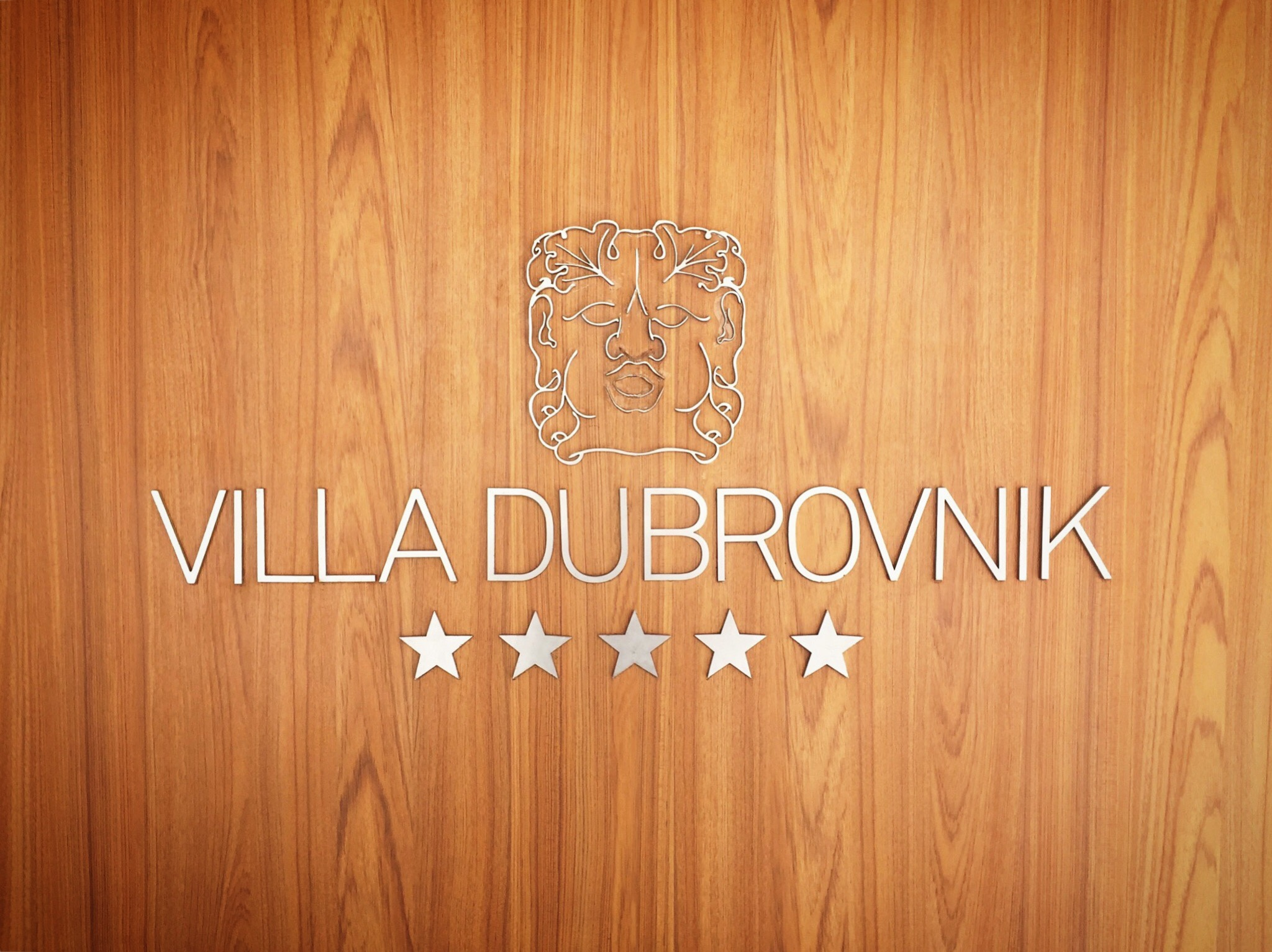 Entrance sign of the hotel villa dubrovnik in coratia. A wooden door with a silver male head outline and five metal stars.