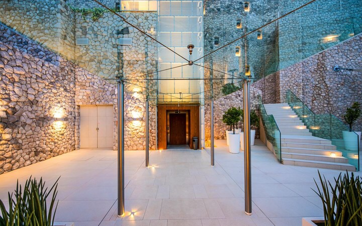 Entrance walkway covered by glass to Villa Dubrovnik hotel, surrounded by stone walls and lit in the evening with soft spotlights