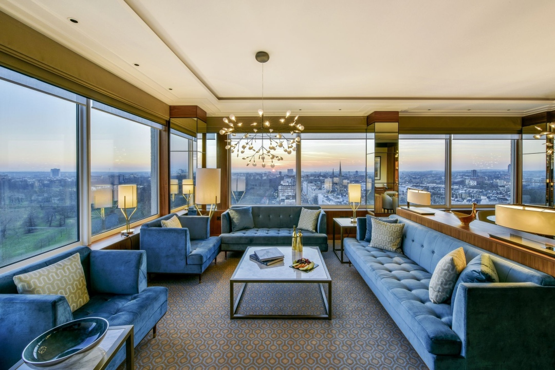Luxury suite at the Royal Lancaster London Hotel with blue velvet furniture and gold lighting at sunset