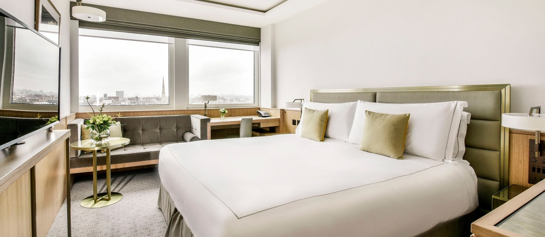 Double bedroom at the Royal Lancaster London Hotel with velvet interior styling and a window overlooking London