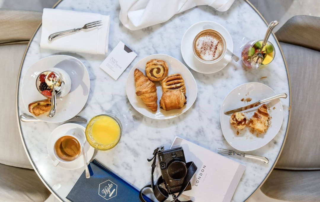 Breakfast served on a round white marble table at the Royal Lancaster London Hotel with croissants, orange juice, berries and coffee