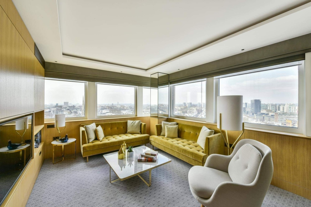 Suite at the Royal Lancaster London Hotel with gold velvet furniture and soft white lighting and windows overlooking london