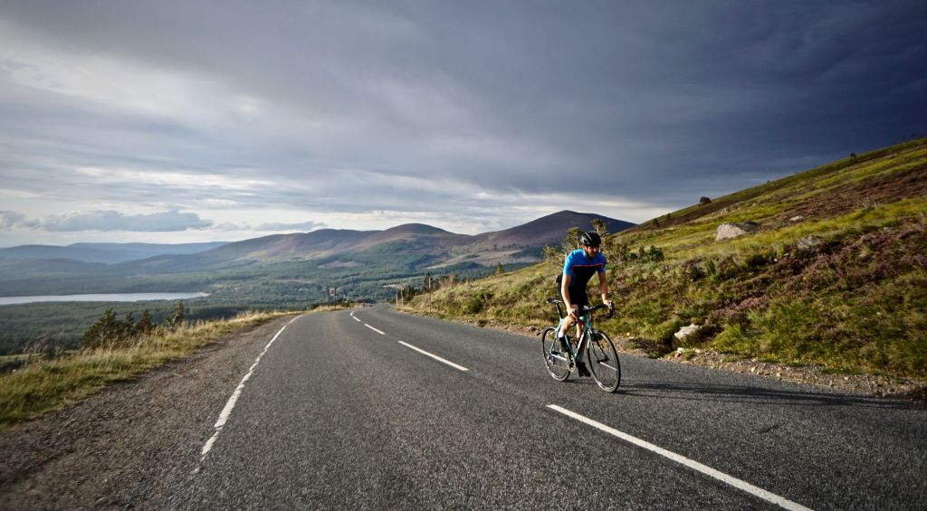Man on a bike wearing a blue jersey cycles up a steep hill in scotland with views of hills behind him