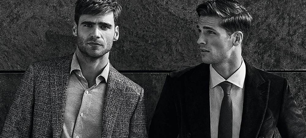Two handsome male models in black and grey suits in black and white