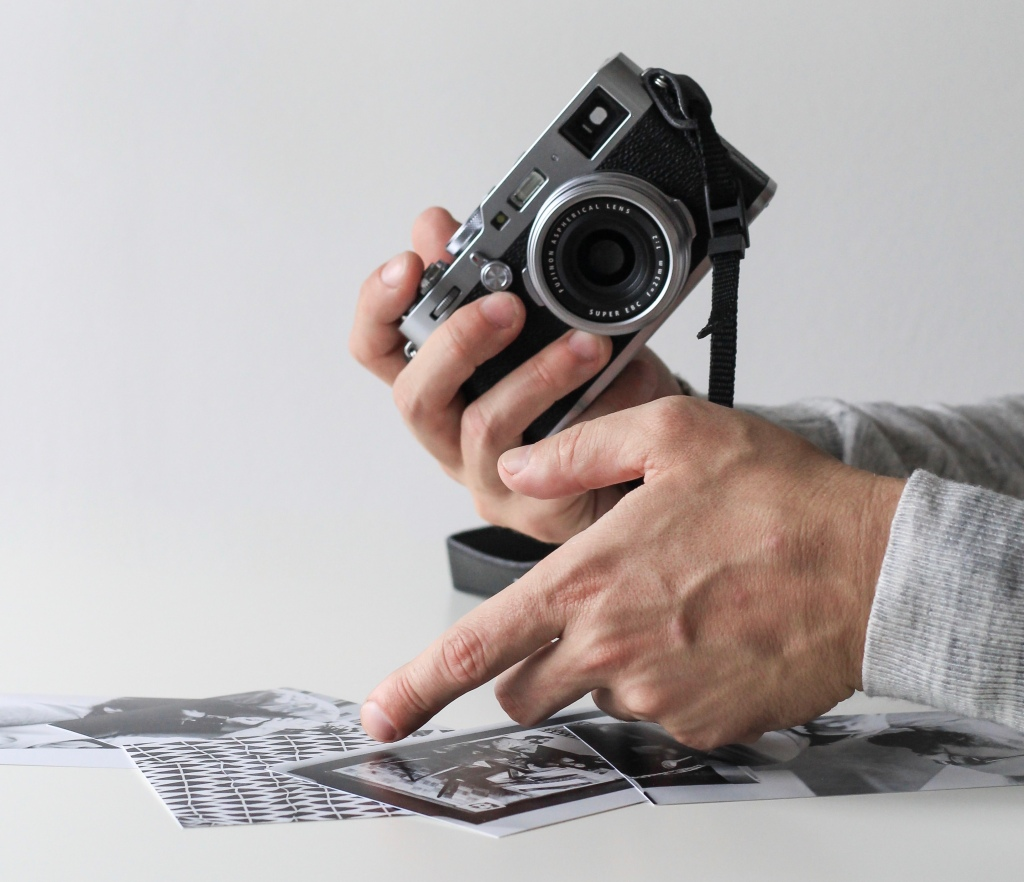 A man's hands holding a manual film camera while sifting through a selection of black and white photos on a white table.