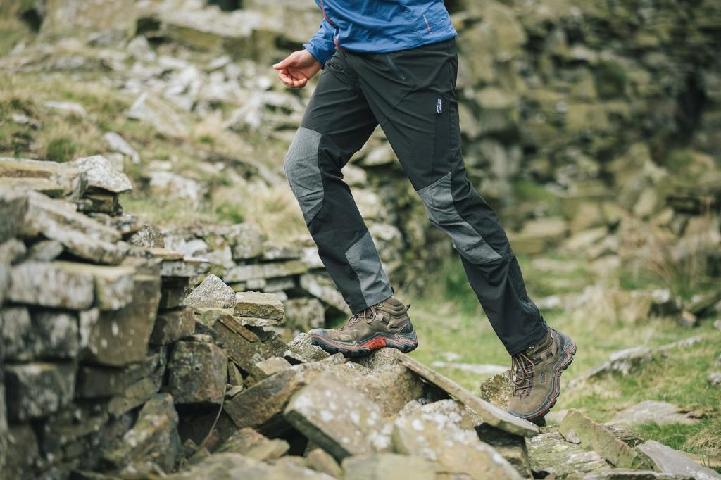 A man in a blue jacket and berghaus outdoor clothing climbing over some rocks at a stone wall.