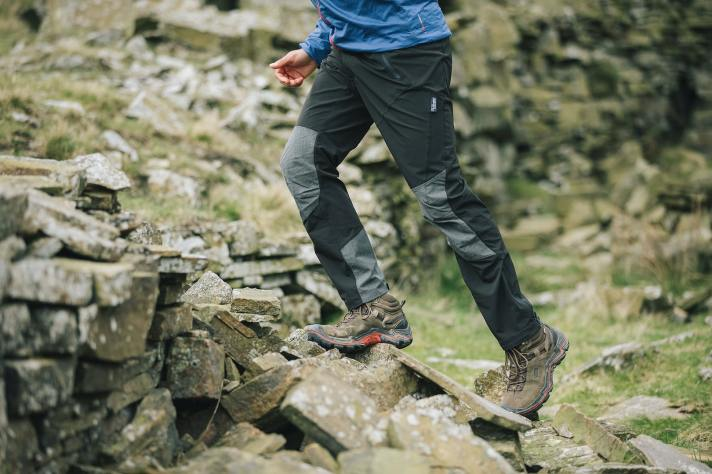 Berghaus Hiking Clothing for Men - with a man climbing a stone wall wearing walking trousers.