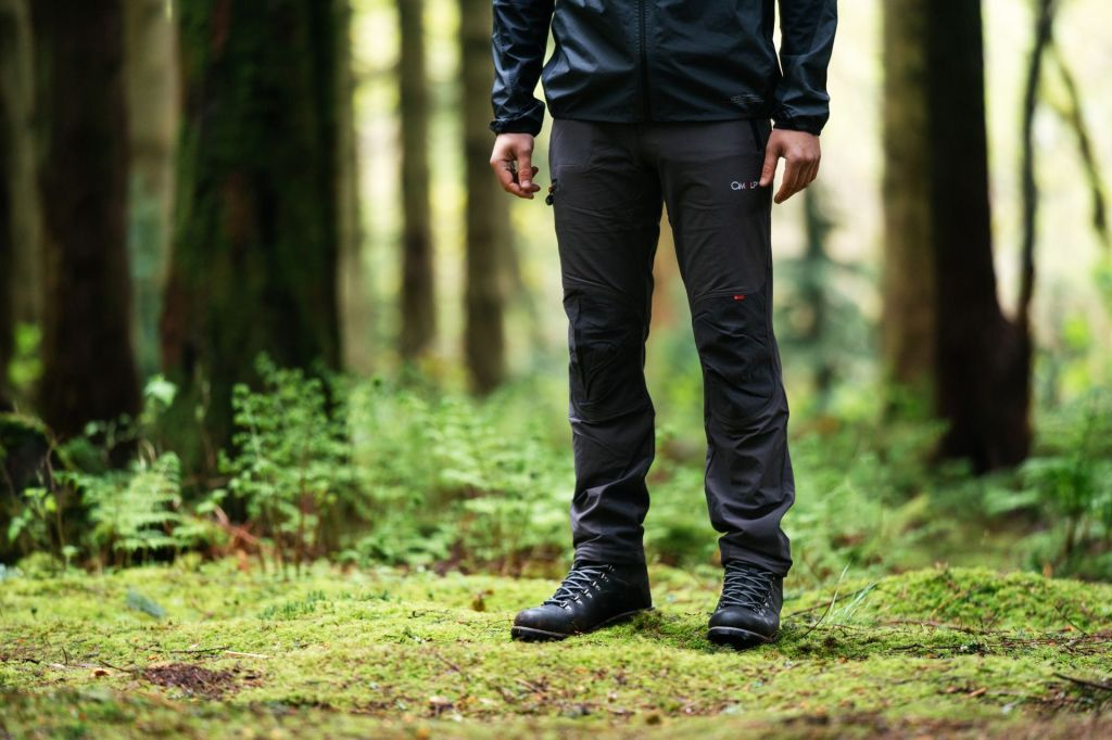 A man wearing berghaus outdoor clothing, stood in a forest setting with trees in the background.