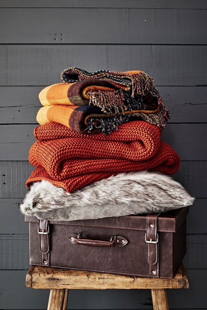 Stack of wool throws in autumn colours on top of a brown leather suitcase on a wooden three legged stool in front of a dark wooden panelled wall
