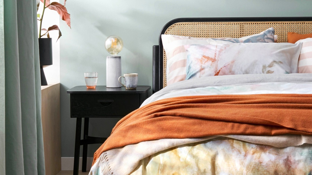 Autumn themed bedroom, with light grey walls, rich orange bed covers and soft furnishings