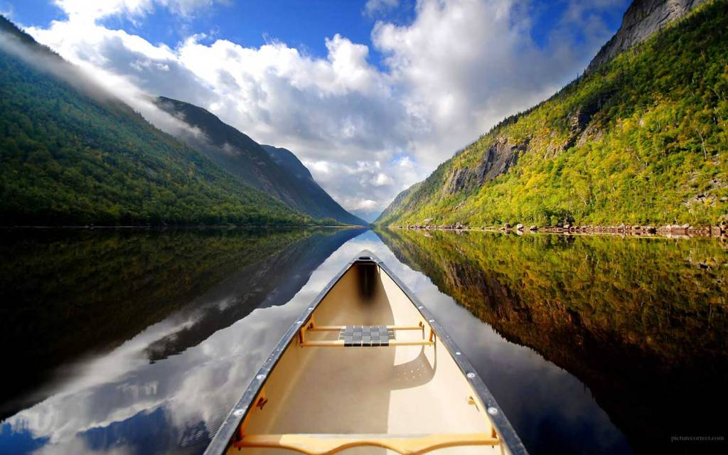 View of the end of a canoe on open water, with a valley on either side.