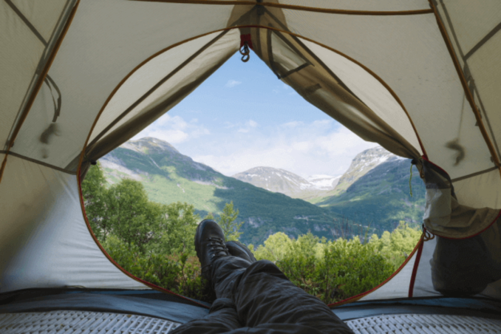 View of feet sticking out of the door of a tent, with a landscape view from high up a mountain in summer.