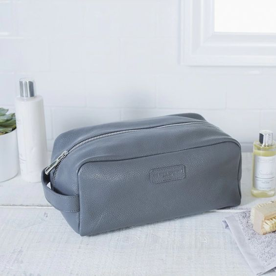 Men's pebblegrain grey washbag for toiletries in a white bathroom.