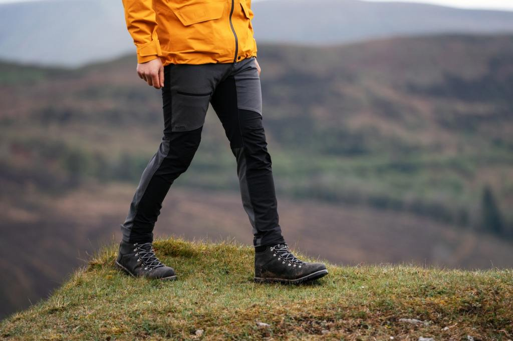 A man in a yellow jacket and black hiking trousers stands on top of a hill, with the landscape in the background.