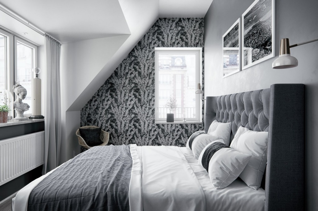 Bedroom interior with a plush grey bed, grey and black wallpaper and accents of white and marble.