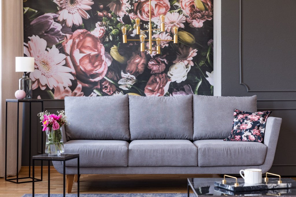 A living room interior with a grey couch and blush floral walls.