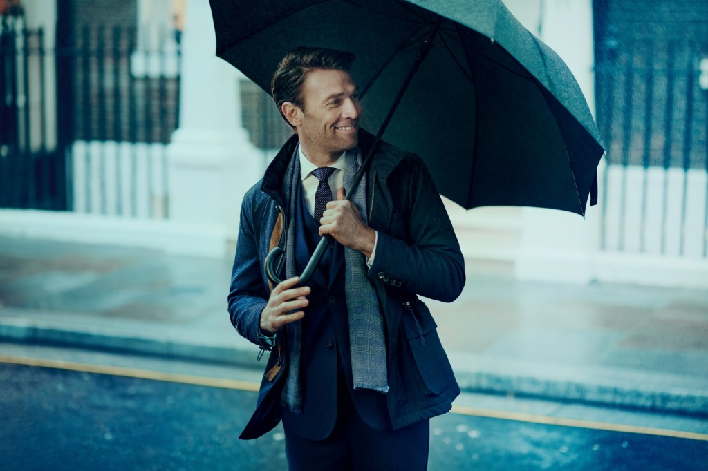 A stylish handsome man in hackett london menswear in the rain holding an umbrella.