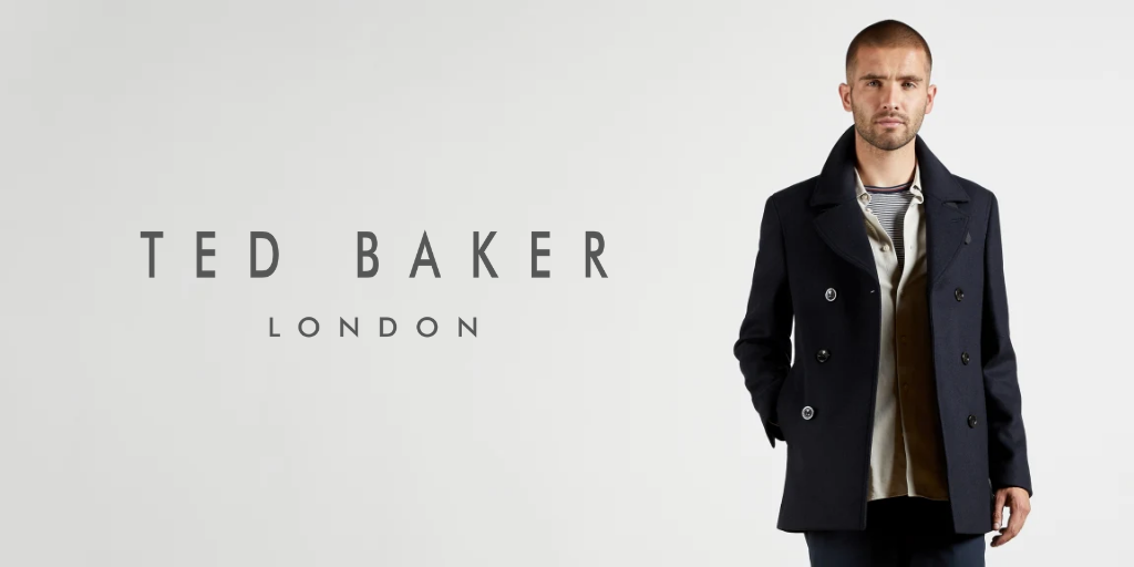 A man in a navy blue coat on a grey background, promotional image for Ted Baker Menswear
