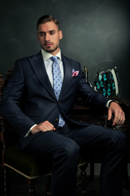 Thomas Fortin Menswear - male model with a silk tie and dark blue suit, top hat and cane on a deep blue background.
