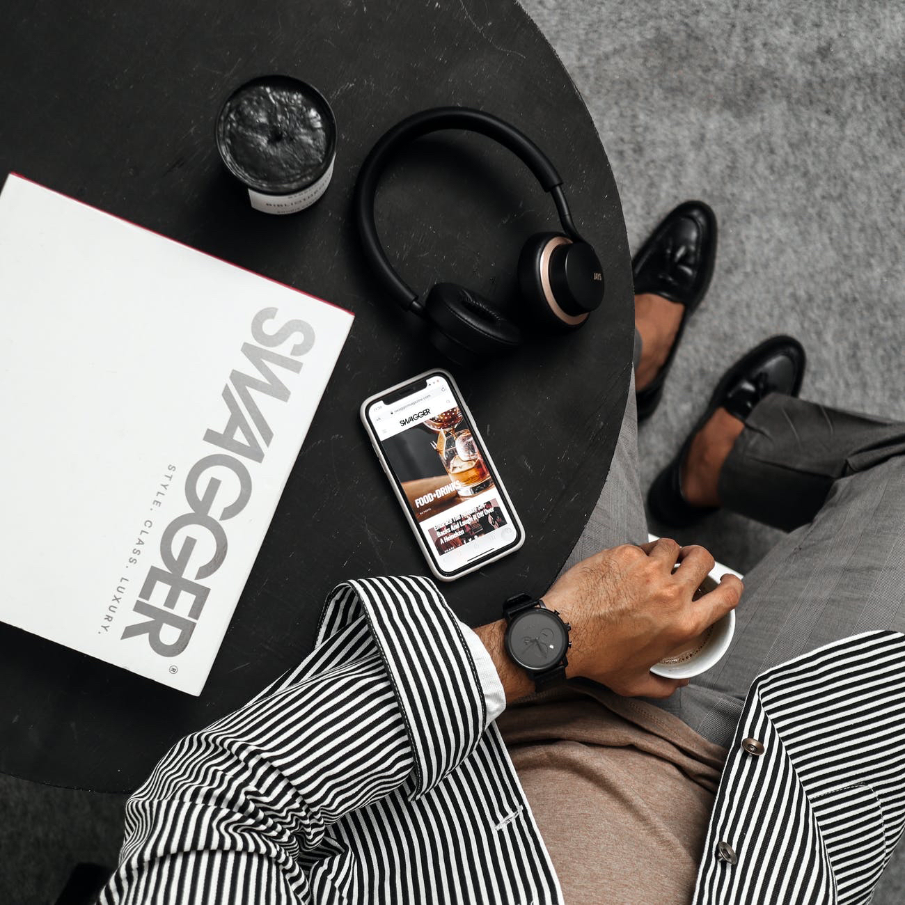 A man in a striped black and white jacket looks at his wrist watch while resting on a table with a coffee, a pair of headphones and an iphone.