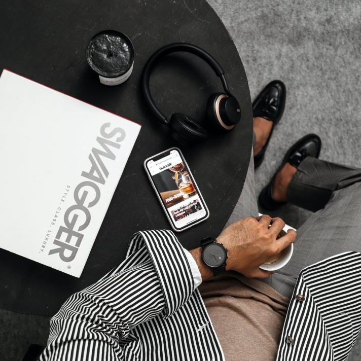 Menswear Inspiration - Man drinking coffee with various technology around him