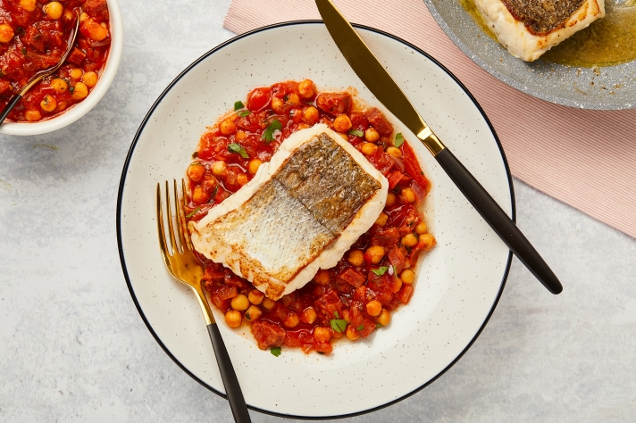 Love Seafood - Hake Fillet with a Tuscan Tomato, Chorizo and Chickpea Stew served on a white plate with gold cutlery.