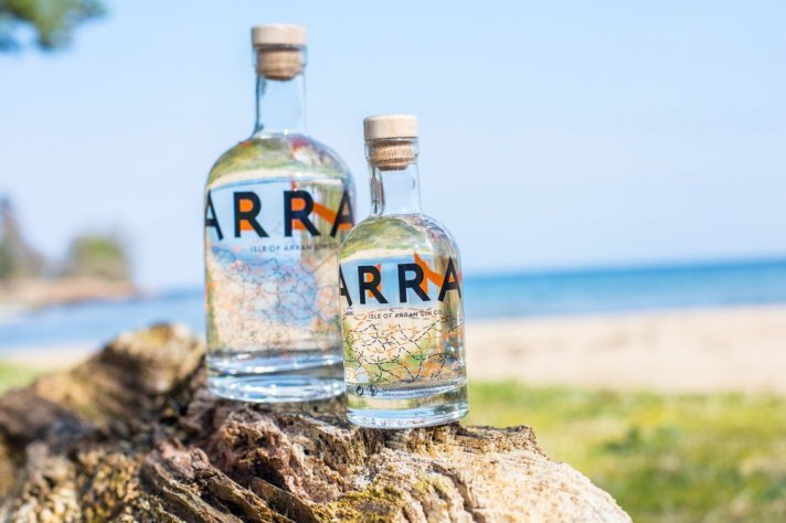 Two bottles of Arran Gin on a wooden log, with a coastal landscape in the background.