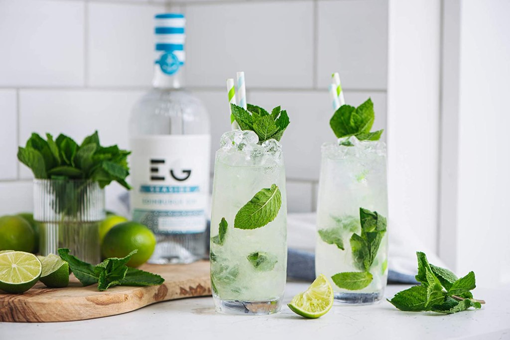 Two gin cocktails in a white tiled kitchen with chopped limes and mint in the background alongside a bottle of seaside gin.