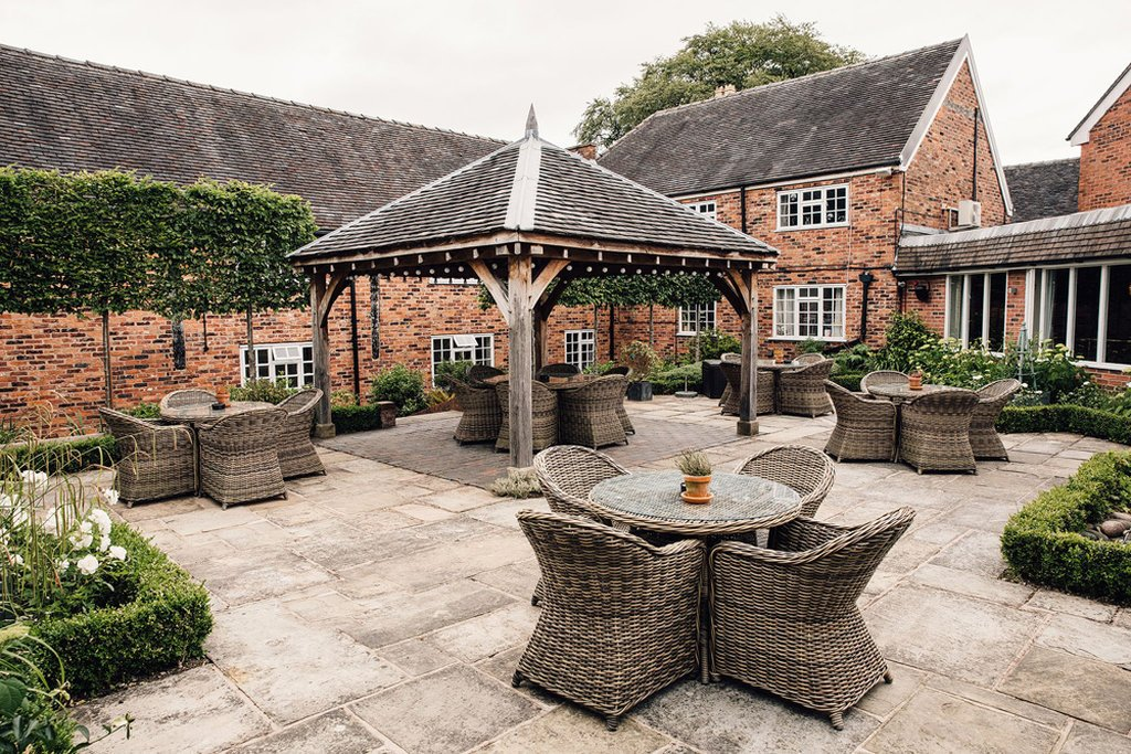 The courtyard at the Manor House Hotel in Alsager, with five outdoor rattan tables and chairs and covered pagoda.
