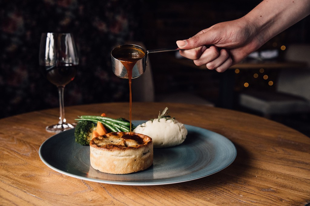 A hand holding a small metal saucepan pours gravy over a pie on a blue plate on top of a wooden table, beside a glass of red wine.
