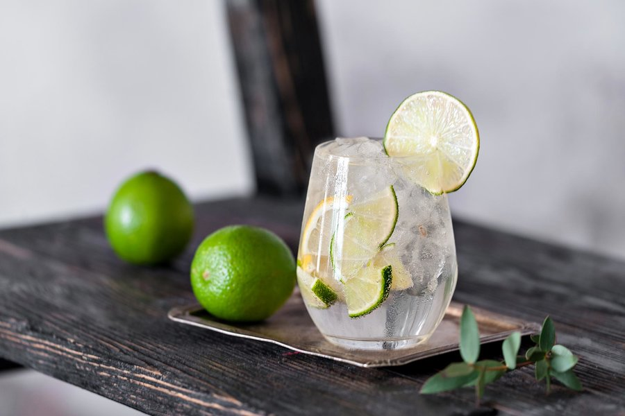 Gin and tonic in a clear glass, served with ice and citrus fruits, alongside limes on a wooden table.