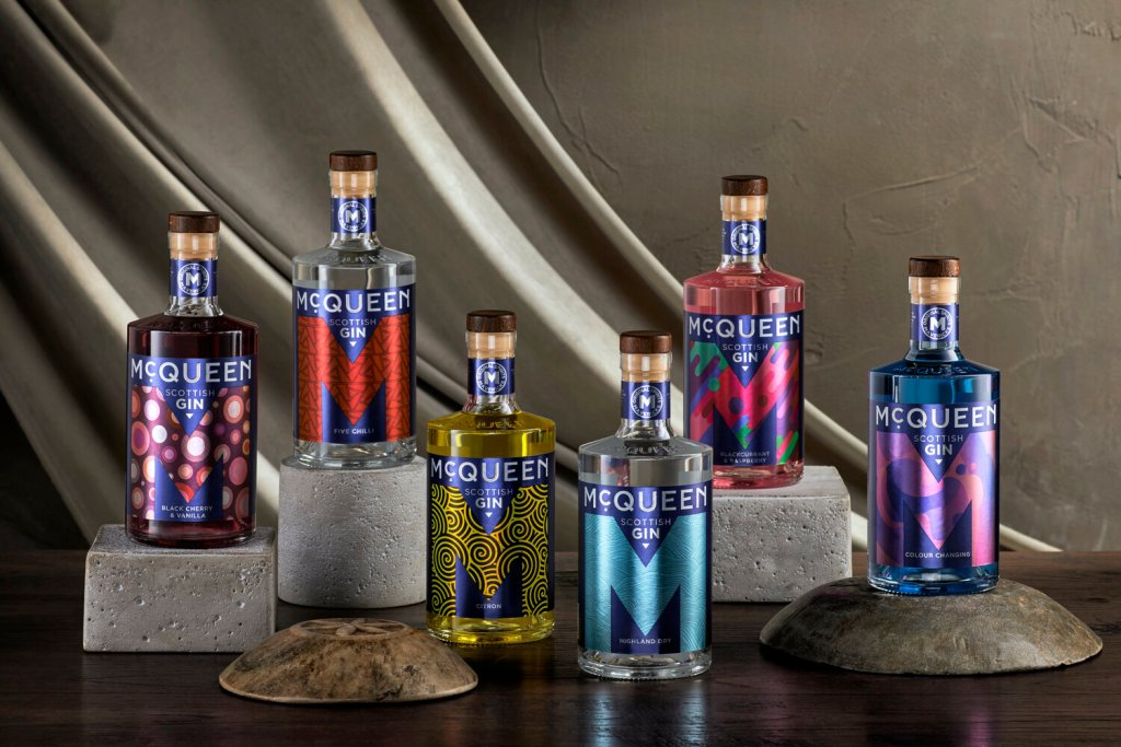 A selection of McQueen Gins on various height boxes in front of a dark grey and concrete background.