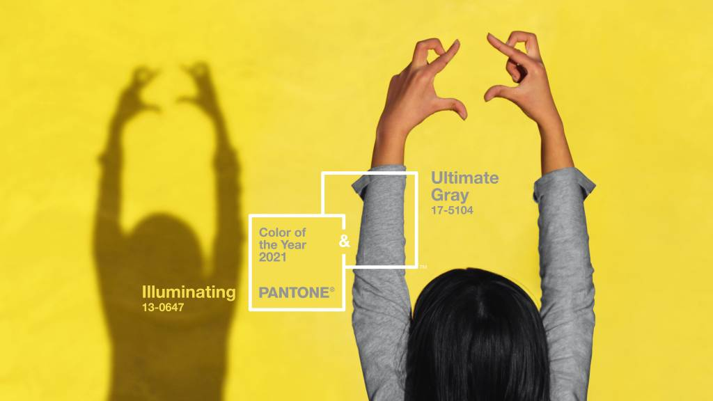 Pantone Colour of the Year 2021 - Ultimate Gray and Illuminating. A woman holds her hands up to frame the colours on a yellow background.