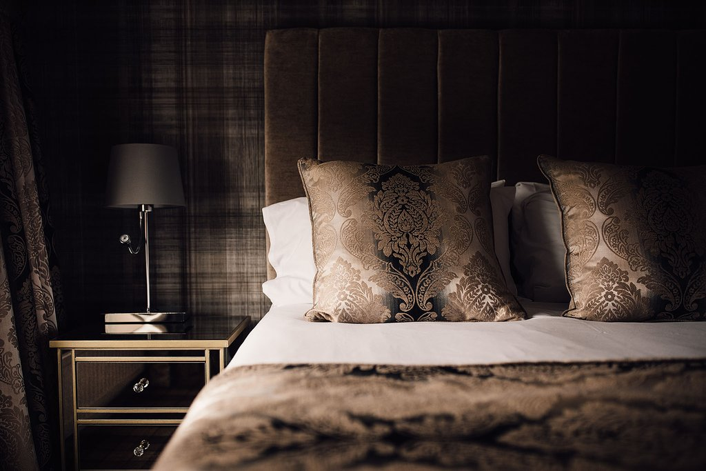 Bedroom interior - with  large double bed, with rich brown fabric, cushions and headboard against brown tartan style wallpaper.