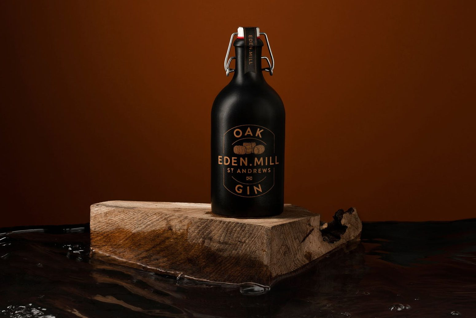 A black ceramic bottle of eden mill oak gin on top of a wooden board, in front of a red-brown background.