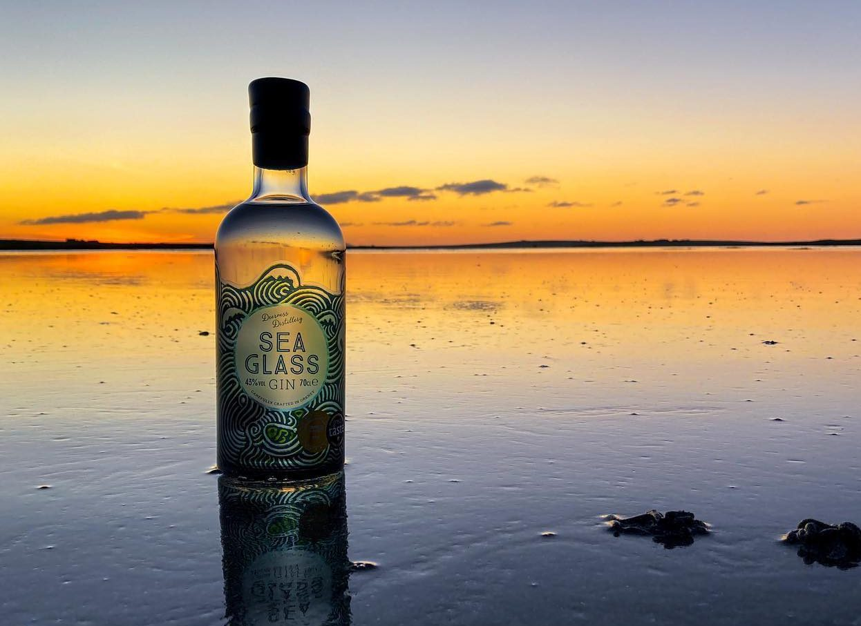 A bottle of sea glass gin at sunset on a beach background. The tide is out and the sun is shining through the glass design on the bottle.