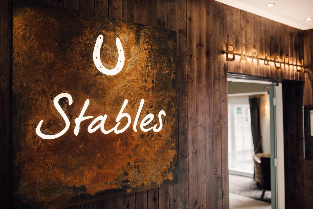 Lit horsehoe and text sign at Stables Bar and Grill in Alsager.
