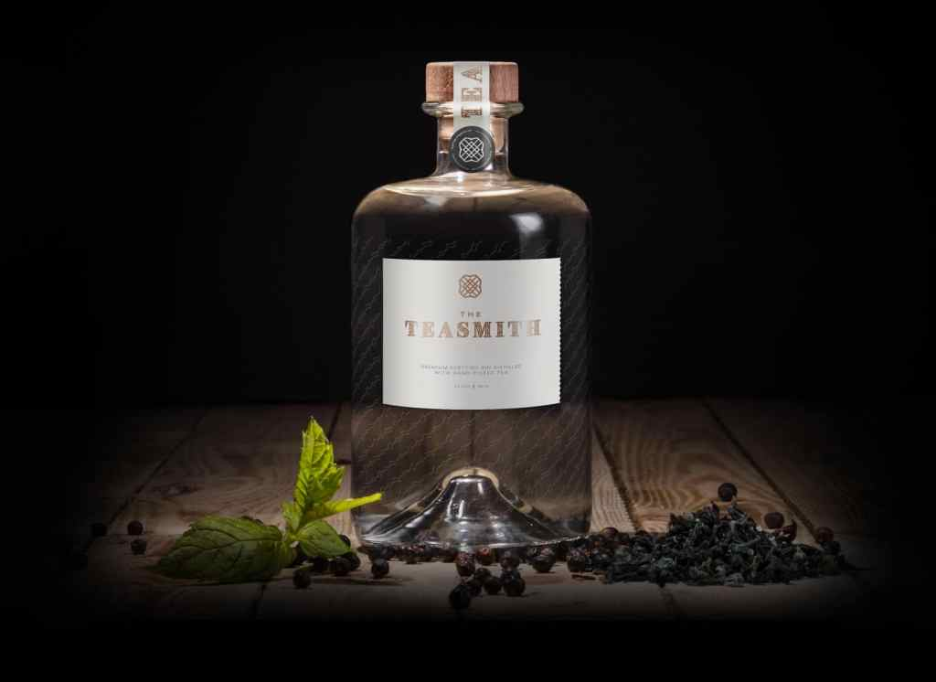 A bottle of teasmith gin on a dark background, with tea leaves and juniper berries next to the bottle. Wooden background can also be seen.