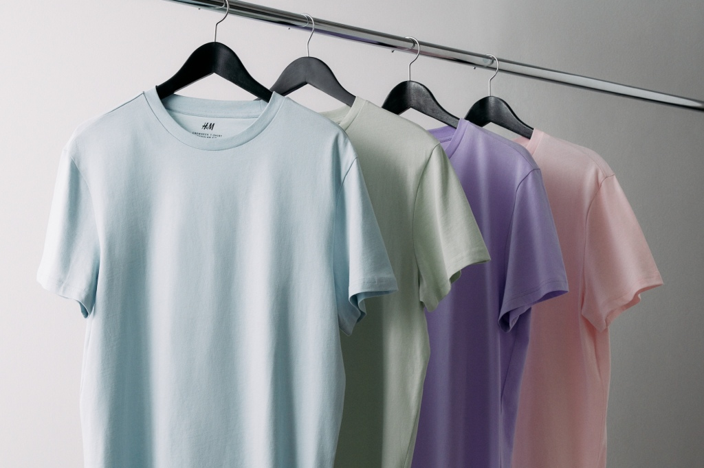 H&M Promotional Image. A selection of  H&M basics mens t-shirts in pastel colours on a clothing rail.