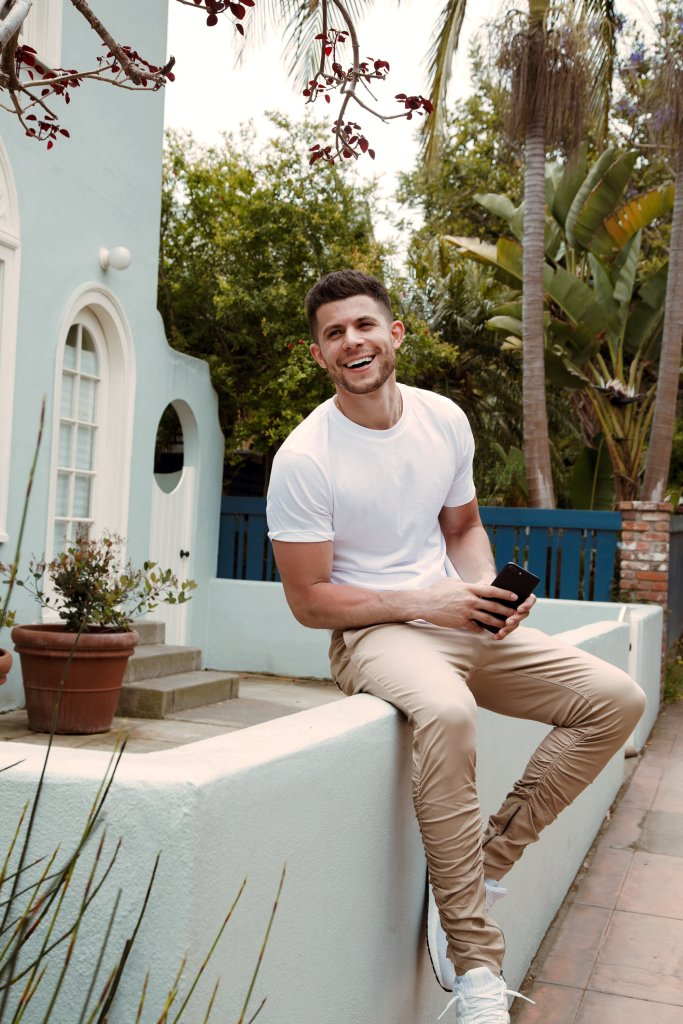 H&M Menswear Promotional Image: A man in a white tshirt and chinos sits on a wall.